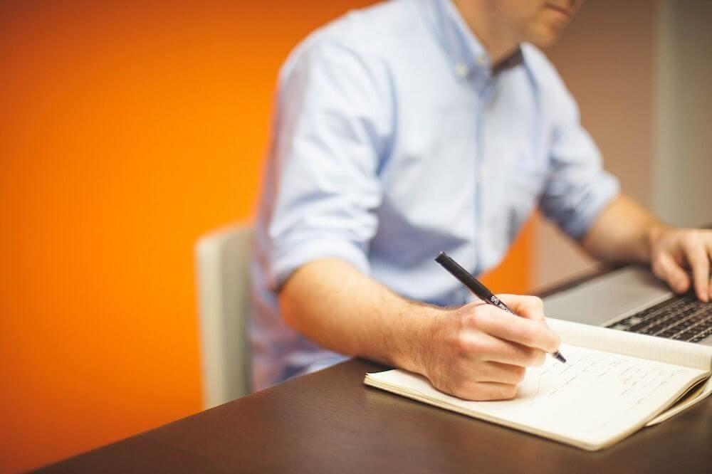 Een man schrijft aan een bureau op kantoor.