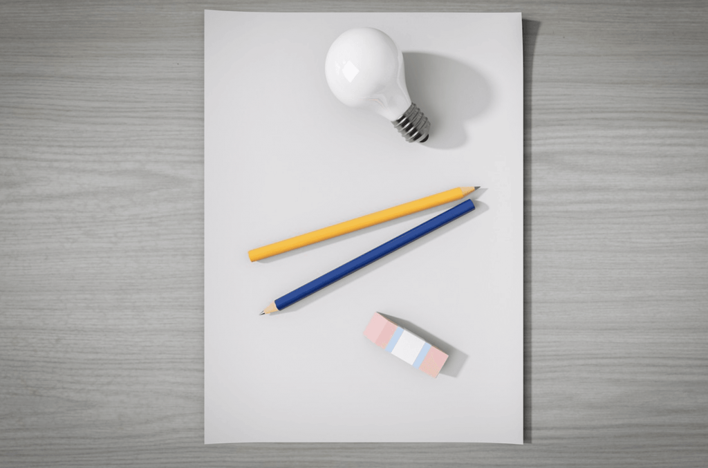 A sheet of paper, two pencils, an eraser and a lamp