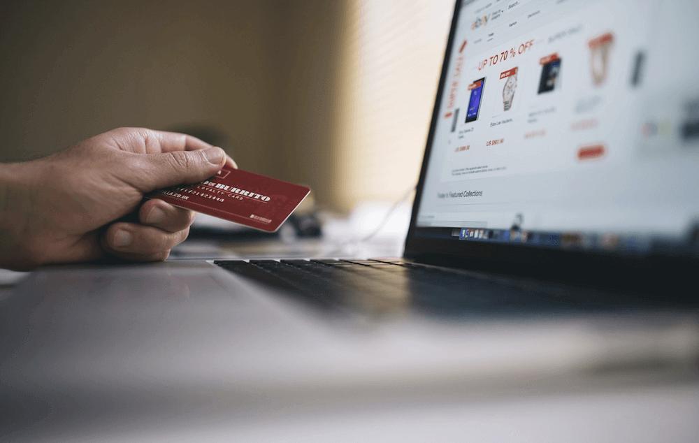 Een webshop op een laptop, met een hand met een betaalkaart ernaast.