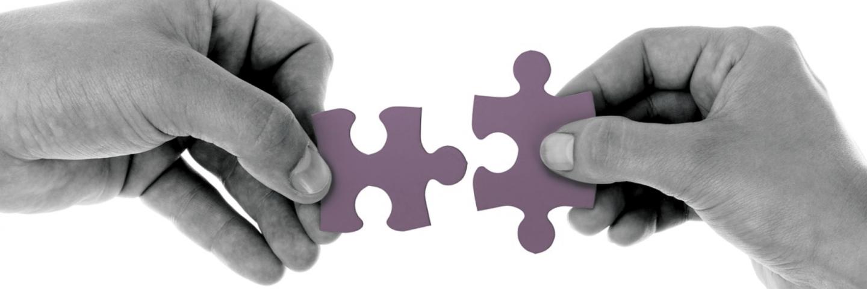 Twee handen met puzzelstukjes