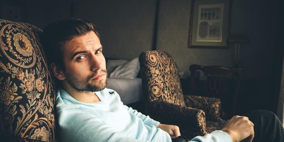 Man in hotel room on a luxurious chair looks thoughtful - is he happy or not?
