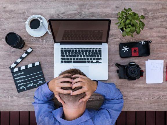 Man met hand in het haar voor een laptop, met camera en filmmateriaal op de tafel