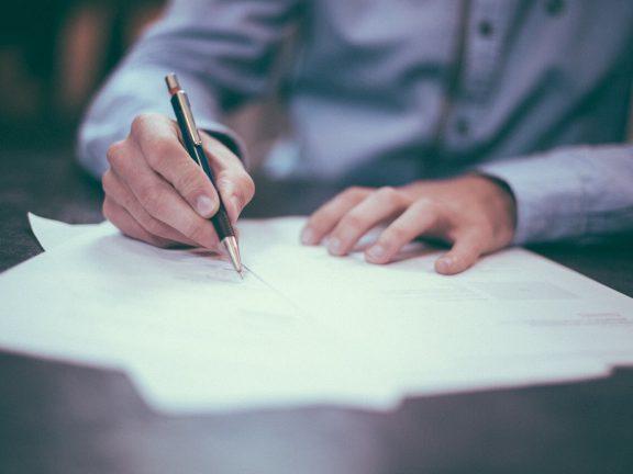 Direct mailing - man schrijft brief met vulppen, draagt overhemd
