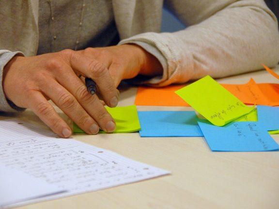 man aan bureau met pen en blaadjes - bedenken direct mailing