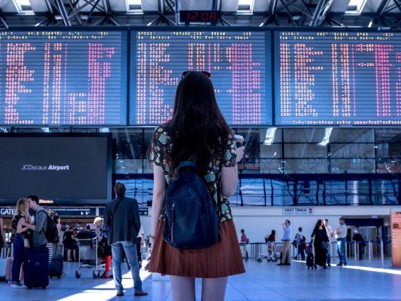 vrouw kijkt naar landingstijden in een vliegveld