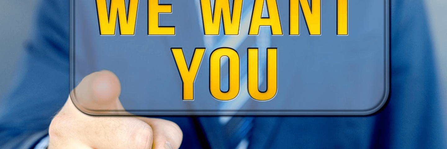 A man in a suit, with the text: 'We Want You'