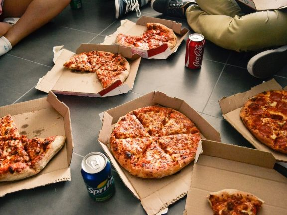 opened pizza boxes with fresh pizza's and cola cans around it with people sitting on the floor