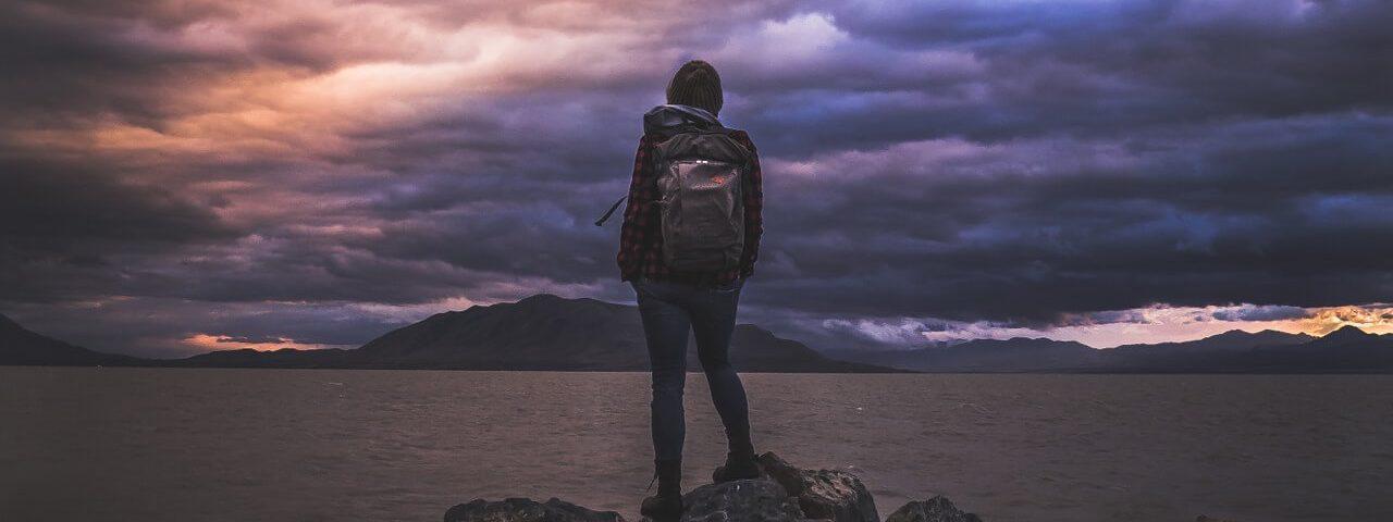 Meisje met backpack voor groot meer. donkere wolken.