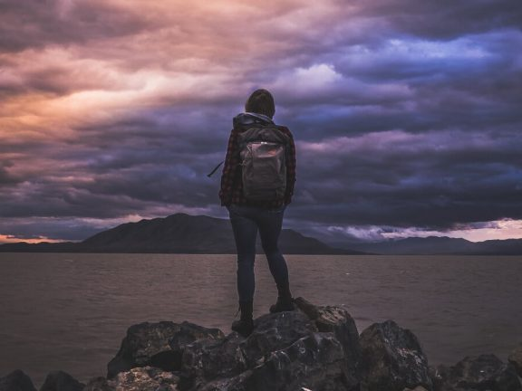 Girl with backpack in front of big lake. dark clouds.