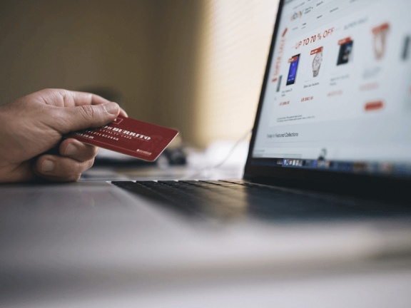 A webshop on a laptop, with a hand with a payment card next to it.