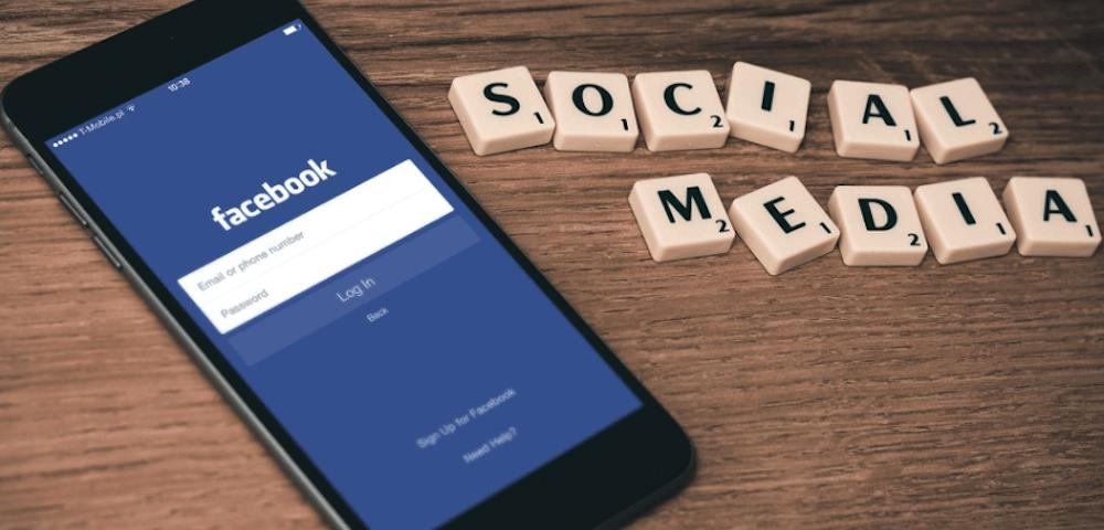 Facebook op een mobiele telefoon, met daarnaast de letters 'SOCIAL MEDIA'