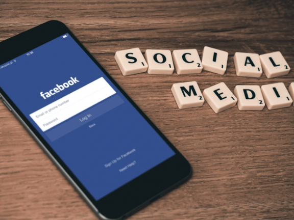 Facebook on a mobile phone, with the letters 'SOCIAL MEDIA'