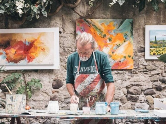 Artist paints standing with work in the background